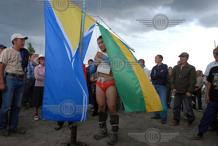 The winner of the khuresh wrestling competition holds the Tuvan flag (left) and the flag of Erzin (right) at festivities for the Tuvan Naadym (New Year) holiday in Erzin. For winning he receives a prize of 1000 Roubles (US $30) and two sheep.