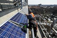 GERMANY Hamburg, IBA exhibition, an old war bunker is changed into an renewable energy project, installation of solar panels / DEUTSCHLAND  Hamburg, Energiebunker Wilhelmsburg , IBA Projekt, Energieerzeugung aus Solarenergie, Biogas, Holzhackschnitzeln und Abwaerme aus einem benachbarten Industriebetrieb, der Energiebunker soll einen Teil des Reiherstiegviertels mit Waerme versorgen und gleichzeitig erneuerbaren Strom in das Stromnetz einspeisen. Der Energiebunker soll circa 22.500 MWh Waerme und fast 3.000 MWh Strom erzeugen. Das entspricht dem Waermebedarf von circa 3.000 Haushalten und dem Strombedarf von etwa 1.000 Haushalten, Montage der Solon PV Module an der Suedseite des ehemaligen Flakbunkers - MORE PICTURES ON THIS SUBJECT AVAILABLE!!