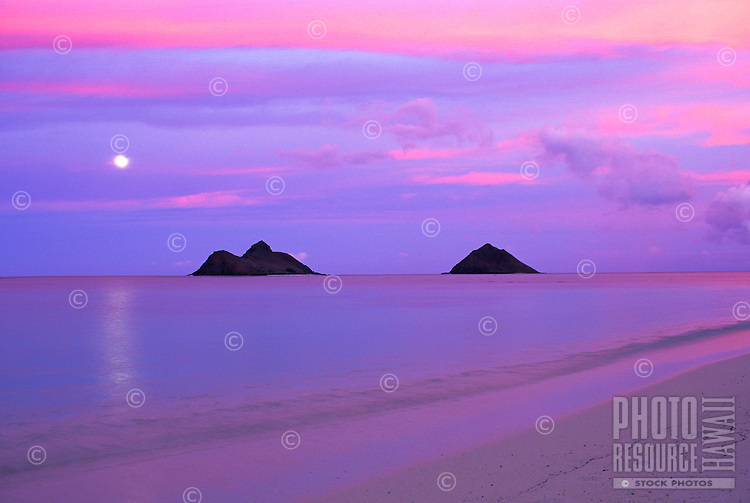 Full Moon rising over the Mokulua Islands in Lanikai while the sun sets over Oahu.