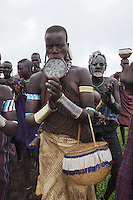"Ethiopia. Southern Nations, Nationalities, and Peoples' Region. Omo Valley. Mursi tribe. Agro-pastoralist group. Nomadic. A group of Mursi women clap their hands in a welcoming sign for foreign visitors. Mursi women are known as ""disk-lip"" women. The bottom lip is slit along its full length and the front bottom row of teeth are pulled out to accomodate the ceramic disk which is handmade with a rim around which the stretched lip is pulled. The women are famed for wearing large plates in their lips (round clay plates placed into a cut in the lower lip) and ears. The disk is seen as a symbol of beauty and wealth, and often the younger girls will pierce and strech their ear-lobes, inserting a matching disk in the extended lobe. The Omo Valley, situated in Africa's Great Rift Valley, is home to an estimated 200,000 indigenous peoples who have lived there for millennia. Amongst them are 8'000 Mursi who dwell between the Omo and Mago rivers. Southern Nations, Nationalities, and Peoples' Region (often abbreviated as SNNPR) is one of the nine ethnic divisions of Ethiopia. 11.11.15 © 2015 Didier Ruef"