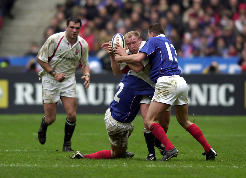Photo.Richard Lane.France v England at Stade de France. 2-3-2002. Lloyds TSB Six Nations Championship..Neil Back is tackled by Raphael Ibanez and Tony Marsh.