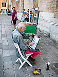 An artist sketches in the street, Venice, Italy