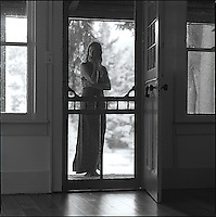 Woman standing behind screen door