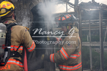 Two firefighters spraying water on a hot spot from a building fire