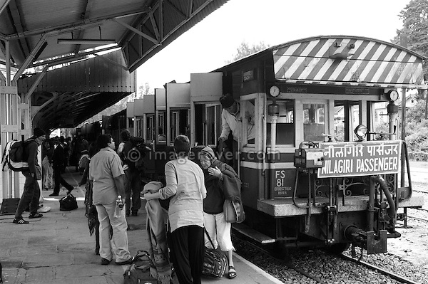 Passengers exiting the Nilgiri Mountain Railway train at Ooty railway station. India, Tamil Nadu, Ooty (Udhagamandalam) 2005. --- Info: The Nilgiri Mountain Railway (NMR) is the only rack railway in India and connects the town of Mettupalayam with the hill station of Udagamandalam (Ooty), in the Nilgiri Hills of southern India. The construction of the 46km long meter-gauge singletrack railway in Tamil Nadu State was first proposed in 1854, but due to the difficulty of the mountainous location, the work only started in 1891 and was completed in 1908. This railway, scaling an elevation of 326m to 2,203m and still in use today, represented the latest technology of the time. In July 2005, UNESCO added the NMR as an extension to the World Heritage Site of the Darjeeling Himalayan Railway.