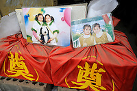 Cinerary casket and photos of Liu Yaqi and Liu Yajia, all 14, twin sisters, who died during the collapse of a building while attending a class in Juyuan Middle School in Dujiangyan, Sichuan, China. More than 500 - 700 students are still buried under the rubble. About 900 students are believed dead during the disaster in this school..18 May 2008