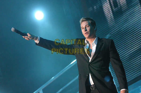 LEE RYAN - BLUE.Perform live in concert at Nottingham Arena,.UK June 28th 2005..half length stage gig music holding out microphone listening ear gesture  .Ref: JEZ.www.capitalpictures.com.sales@capitalpictures.com.©Jez Self/Capital Pictures
