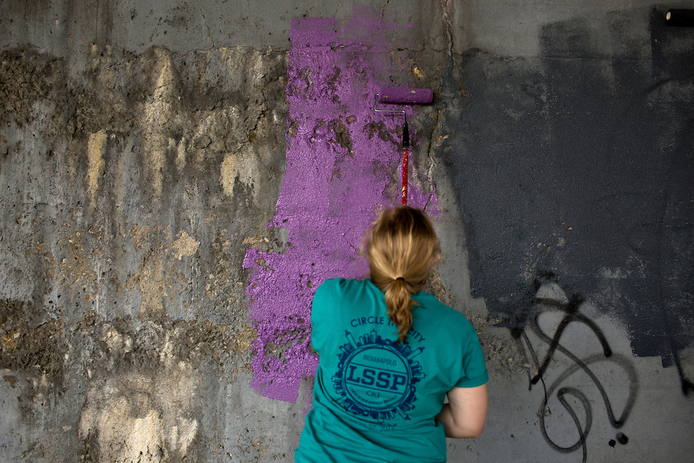 """Members roll on a fresh coat of paint under a train bridge during """"Circle the City with Service,"""" the Kiwanis Circle K International's 2015 Large Scale Service Project, on Wednesday, June 24, 2015, in Indianapolis. (Photo by James Brosher)"""