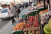 """A man and a woman walks by a fruits and vegetables store in the Greenpoint neighborhood of New York City borough of Brooklyn, NY, Monday August 1, 2011. Greenpoint is sometimes referred to as """"Little Poland"""" due to its large population of working-class Polish immigrants, reportedly the second largest concentration in the United States after Chicago."""