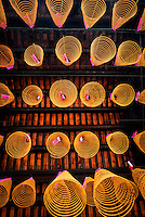 Conical incense coils hanging on wires below the roof at Chua Thien Hau Temple in Cho Lon, Ho Chi Minh City, Vietnam.<br />