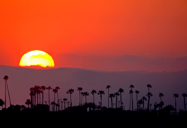 The sun sets behind the approaching fog from the Pacific Ocean near Long Beach California