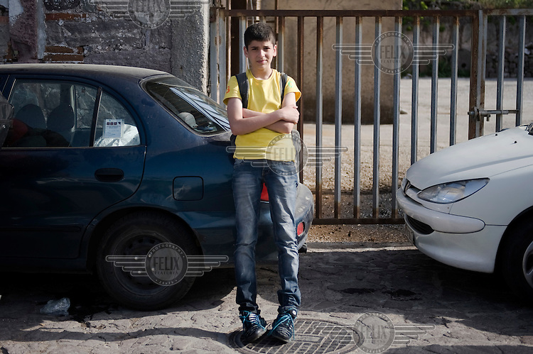 15 year old Sharaf from Damascus stands by a parked car in Skala Sykaminias after his arrival in Lesbos island by inflatable boat from Turkey. He has been traveling on his own since his family was killed in the Syrian civil war. <br /> Every day hundreds of refugees, mainly from Syria and Afghanistan, are crossing in small overcrowded inflatable boats the six mile channel from the Turkish coast to the island of Lesbos in Greece. Many spend their life savings, over $1,000, to buy a space on these boats.