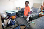 CAPE TOWN, SOUTH AFRICA - MARCH 15: Sikhumbuzo Hlahleni, age 15, a student at Cape Town City Ballet's youth company looks in a suitcase that contains all his belongings in his family house on March 15, 2010 in Khayelitsha, South Africa. He trains in Cape Town every Saturday. He also trains a few days week at home in Khayelitsha, a poor township outside Cape Town. He has to change taxi three times to get to the school. (Photo by Per-Anders Pettersson)...