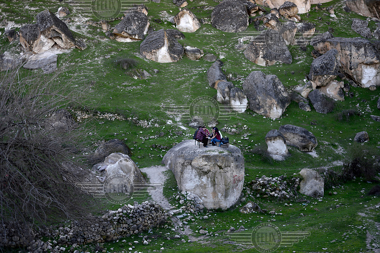 People picnicking on a huge boulder popular with locals and tourists near Hasankeyf. 80% of the town will be submerged beneath 60 metres (200 feet) of water following the completion of the Ilisu hydroelectric dam, 96 kilometres (60 miles) downstream on the Tigris River. The reservoir created by the dam will be approximately of 313 km2 (121 sq mi) and will flood several villages as well as Hasankeyf.