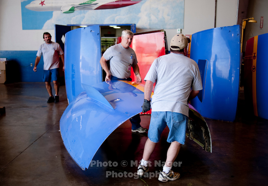 Timothy Regnold (cq, middle) and other Southwest Airlines employees move an engine cowling after a repair in the maintenance facility of Southwest Airlines facilities near Love Field Airport in Dallas, Texas, Wednesday, October 27, 2010...PHOTO/ MATT NAGER