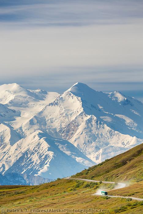 Tour bus travels the Denali park road through thorofare pass, with Denali visible along the Alaska Range horizon.