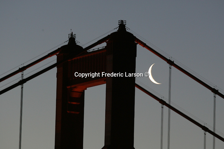 The crescent moon set behind the Golden Gate Bridge with San Francisco skyline in the background.