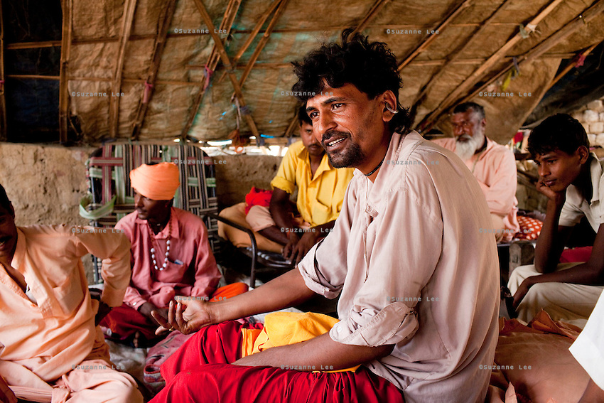 "Snake charmer Baba Prakash Nath (center, in red & white), 35, sits in a temporary camp of travelling snake charmers from Rajasthan who have pitched camp in remote Lodha Basti, Manana village, Samalkha town, Haryana, India on 15th June 2012. ""The government banned our trade but didn't give us any alternative options of livelihood,"" says Baba Prakash Nath. India's traditional snake charmer communities suffer from a loss of livelihood because of stringent wildlife laws and  are forced to resort to begging or working as daily wage labourers. A new program to encourage the snake charmer's children to attend school is underway, to keep them from becoming daily-wage child labourers or joining their parents in scavenging and begging in cities. Photo by Suzanne Lee for The National"