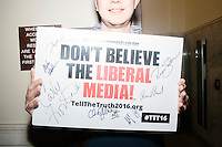 "Conservative activist Bryan Tupper, of Greenwood, South Carolina, holds up a sign reading ""Don't Believe the Liberal Media"" and signed by many of the 2016 Republican presidential candidates as he waits outside the Secretary of State's office before Republican presidential candidate Dr. Ben Carson arrives to officially file his presidential candidacy in the New Hampshire State House in Concord, New Hampshire."
