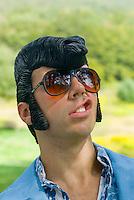 Man in leisure suit wearing rubber Elvis wig