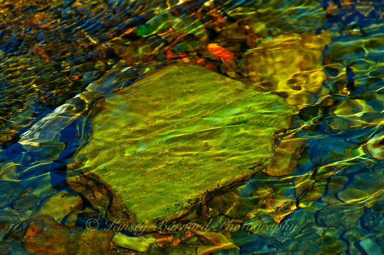 Water flows over rocks in Graves Creek near Hungry Horse Reservoir creating a shimmering pallette of colors