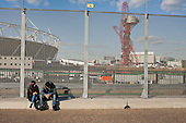 Two people rest by the security fence alongside the Olympic Stadium and Anish Kapoor's ArcelorMittal Orbit sculpture, London 2012 Olympic Park, Stratford.