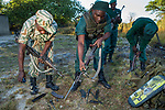 Anti-poaching scouts cleaning rifles before deployment, Kafue National Park, Zambia