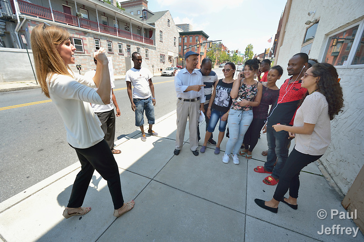 Penny Gushiken (left) takes a photo of her cultural orientation class for newly arrived refugees on a sidewalk in Lancaster, Pennsylvania. The class was engaged in a scavenger hunt of sorts, tasked with finding people engaged in specific activities such as eating, listening to music, and taking out trash. In this case, the class was supposed to find someone talking on the phone. When they did, Gushiken took a photo of the group posing with her. The class is sponsored by Church World Service. <br /> <br /> Photo by Paul Jeffrey for Church World Service.