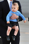 AUSTRALIA, Canberra : Britains Prince George is carried by his father Prince William during their arrival at Defence Establishment Fairbairn, Canberra on April 20, 2014. Britain's Prince William, his wife Kate and their son Prince George are on a three-week tour of New Zealand and Australia. AFP PHOTO / Mark GRAHAM