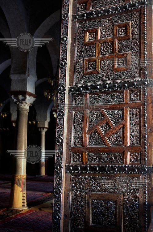 Ornately carved wooden door into the Mosque of Sidi Oqba (The Great Mosque), displaying both natural and geometric designs.