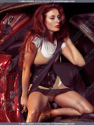 Beautiful young woman in a trendy outfit getting out of a crashed car. High fashion photo.