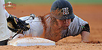 Left fielder Jack Colton (9) of the Harvard Crimson gets a face full of dirt as he slides back to first to avoid the pickoff tag of first baseman Ryan Krill (22) the Michigan State Spartans on Saturday, March 15, 2014, at Fluor Field at the West End in Greenville, South Carolina. Michigan State won, 4-0. (Tom Priddy/Four Seam Images)