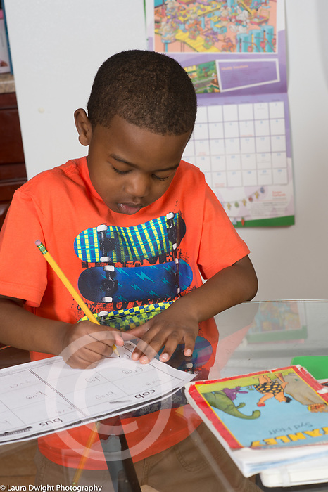 5 year old boy at home in kitchen doing homework ELA writing assignment (English Language Arts)