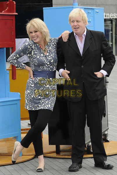 JOANNA LUMLEY & BORIS JOHNSON (Mayor of London).The launch of the old furniture recycling scheme, The Scoop, More London, the Queen's Walk, London, England..July 12th, 2010.full length black suit grey gray white print top blue waist belt trousers leggings leaning on shoulder hands in pockets on hip hand.CAP/CAN.©Can Nguyen/Capital Pictures.