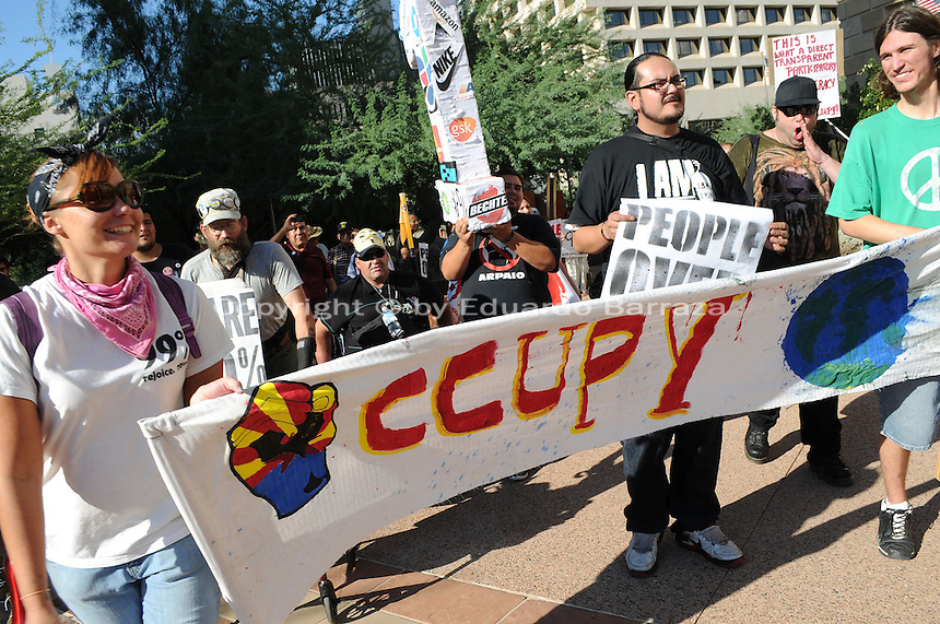 Phoenix, Arizona. September 17, 2012 - A small crowd of demonstrators in Phoenix, Arizona gathered to mark one year since the beginning of the Occupy Movement that opposes Wall Street and large corporations that represent the one percent who control wealth in the United States. In this photograph, activists Rachel Skaggs (left), Orlando Arenas (second from right) and Michael Nehl Royeran (far right) -with the Occupy Phoenix group- lead the march around Downtown Phoenix. Photo by Eduardo Barraza © 2012