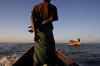 Out with canoe fishermen.  Guy in the prow of the boat (many photographs) is:  Modou Ngom  address: MBour Serere Kaw Senegal   Can call him on his friends cell phone: +221 957 1746..Fishermen coming in and out of port at MBour, Senegal.  Everyone we talked to said the fishing was very poor compared to other years and that they were getting very few fish...There are more net fishermen in this area.  MBour is second only to Dakar in growth.  It is on trade routes from various countries and the fishing is good...600,000 Senegalese participate in the fishing industry.  When you multiply that number times the 6 or 7 kids they each have and other dependents, you can see that this is a significant percentage of the 12 million Senegalese.  Eighty percent of the fish caught are caught by artesinal fishermen.