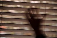 Hand against window shade