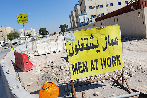 20.12.2014 Doha Qatar. FIFA World Cup 2022 Men at work  sign on a deserted sidewalk in front of the athlete quarters buildings