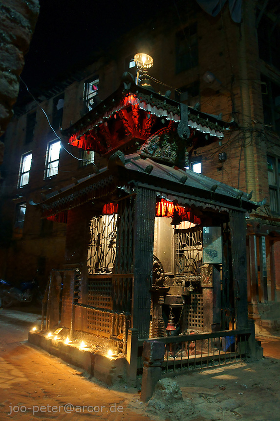 temple in the night in  Dashein festival time in Newar city Bhaktapur in Kathmandu valley, Nepal, October 2011, creating a magic atmoshere with candle light burning wit holy, purified butter and red - white electric lights.