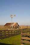 Aermotor windmill over wooden barn; corrals in California's Central Valley
