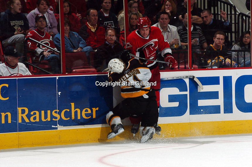 Carolina Hurricanes' Aaron Ward, right, puts a hit on the Boston Bruins' P.J. Axelsson during their game at the RBC Center in Raleigh, NC Wednesday, March 1, 2006. Axelsson left the game after the hit, and the Hurricanes won 4-3...