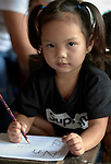 A girl works on an assignment in a preschool sponsored by the Kapatiran-Kaunlaran Foundation (KKFI) in Pulilan, a village in Bulacan, Philippines.<br /> <br /> KKFI is supported by United Methodist Women.