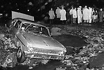 A storm-battered car comes to rest on rocks in Naugatuck, June 1982.