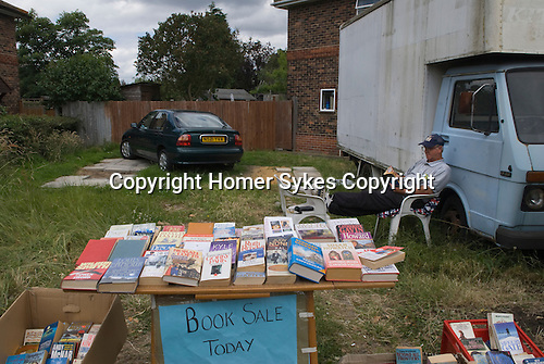 Family selling books as they are moving come, Merton SW20 London 2008.