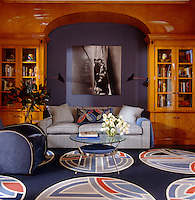 The Biedermeier-style library is panelled in tiger maple and has a photograph of the Rolling Stones by Gered Mankowitz hanging above the sofa