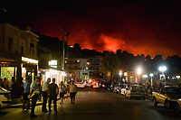 Pictured: Flames seen from the seaside village of Agioi Apostoloi.<br /> Re: A forest fire has been raging in the area of Kalamos, 20 miles east of Athens in Greece. There have been power cuts, country houses burned and children camps evacuated from the area.