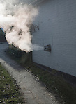 Heat steam emissions from domestic oil powered boiler heating system released through wall of house into the air