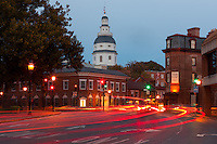 Evening traffic on Church Circle in Annapolis, Maryland creates streaks of light in front of the Maryland State House, opened in 1772, the oldest US state capitol in continuous legislative use, and the historic Maryland Inn, which dates from the same time period.