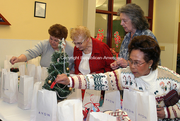 MIDDLEBURY, CT. 10 DECEMBER 11_NEW_121008DA02.jpg-From left, Helga Meikis, Jennie Vendetti, Joan Lombardo, and Ophelia Crane,  look over raffle items during an annual Middlebury Senior Center holiday party held at the Shepardson Community Center on Wednesday. <br /> Republican/American   Darlene Douty