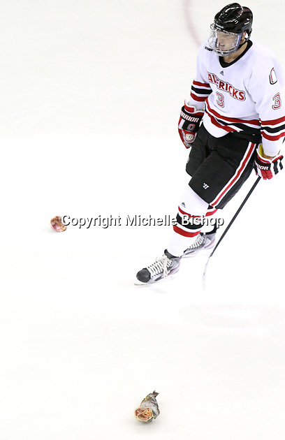 Nebraska-Omaha's Andrej Sustr (3) skates between pieces of a fish thrown onto the ice after a goal. Colorado College defeated Nebraska-Omaha 5-2 Saturday night at CenturyLink Center in Omaha. (Photo by Michelle Bishop) .